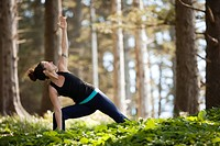 Young Woman in Yoga Pose in Meadow of Evergreen Trees, Oswald West State Park, Oregon, USA