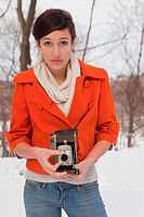 Teenage girl holding vintage camera, portrait
