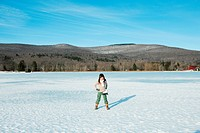 Girl standing in snow with ice skates