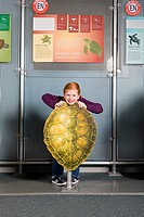 Girl standing behind kemps ridley sea turtle shell