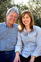 Photograph of a happy heterosexual couple close together, she is younger and he is older.