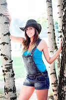 beautiful girl in cowboy hat near birch