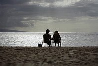 Couple relaxing in chairs on the beach
