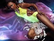 Beautiful black woman wearing a yellow swimsuit lying in shiny water