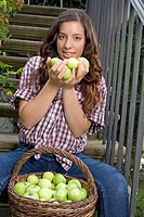 young woman sat on steps with a basket of apples