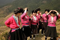 Women of the Yao minority with baskets, traditional costumes and their characteristic hairstyle at the village Ping An near Longsheng, Guangxi, China,...