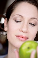 Young woman holding green apple, close_up
