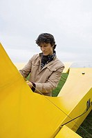 Young man standing by airplane