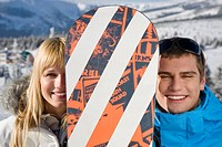 Young couple holding snowboard, portrait