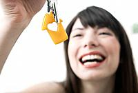 Germany, Cologne, Young woman holding house keys, smiling, close up