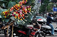 Seoul (South Korea): a man carrying a big wreath on his motor-bike