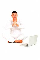 man dressed in white sitting on the floor practicing yoga with laptop