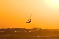 A windsurfer jumps of a wave into the sunset
