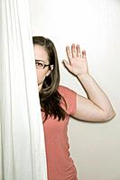 Young woman, wearing glasses, looking out from behind a curtain