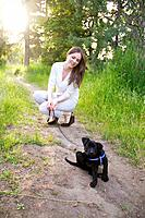 A young woman outdoors with a black lab puppy in Spokane, Washington, USA