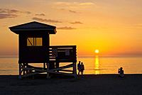 Life guard stand and people silhouetted aganist orange sunset sky over Gulf of Mexico from Venice Beach Florida