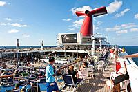 Cruise passengers watching big screen tv outside on deck of Carnival's Triumph cruise ship in the Gulf of Mexico