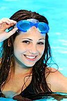 pretty woman with swimming goggles in pool