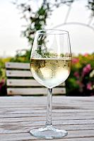Glass of white wine on wooden table in Heuriger Grinzing Vienna