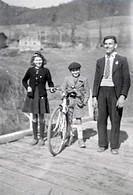 adult man and two children posing on a wooden bridge in the countryside 1950s out of focus