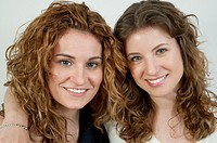 Two young women smiling and looking at the camera. Close view.