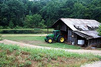 tractor in old worn battered traditional farm building in clearing in forest hurricane mills tennessee usa