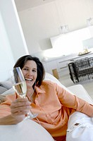 Portrait of a mature woman listening to music and holding a champagne flute