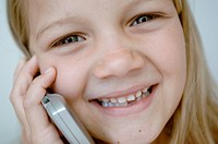 Portrait of a girl talking on a mobile phone and smiling