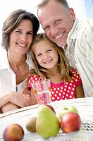 Portrait of a mid adult couple and their daughter smiling with fruits before them