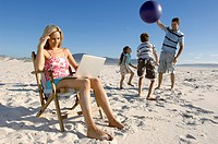 Mid adult woman using a laptop with her family playing on the beach