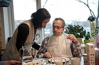 An elderly resident of a nursing home having breakfast at the communal breakfast table, while being helped out by a nurse.