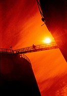 Oil refinery gantry. Oil refinery worker traversing a gantry between two oil storage tanks at a refinery. The setting Sun in the background can repres...