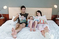 Mid adult couple with their daughter lying on the bed and reading books