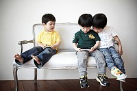 young asian boys playing mobil phone game, South Korean