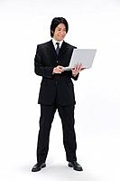 Young businessman holding laptop, white background