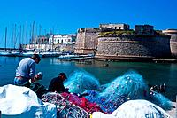 Fishermen mending colourful nets in harbour with sailboats moored beneath medieval stone walls of Gallipoli, sunny spring morning with blue sky, Salen...