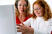 Close_up of a mother sitting with her daughter and using a laptop