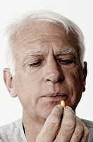 Close_up of a senior man taking a capsule