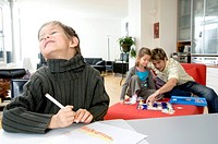 Close_up of a boy holding a color pencil with his father and his sister playing behind him