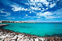 View of Otranto harbour with clear green water, moored sailboats and motorboats, town beyond, sunny spring morning with dramatic clouds in blue sky, S...