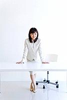 Businesswoman leaning on desk