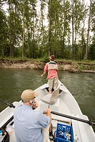 Young man using cell phone while fly fishing on the Elk River from a dory, Fernie, East Kootenays, British Columbia, Canada.