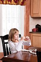 USA, Illinois, Metamora, girl 6_7 making popcorn Christmas ornament