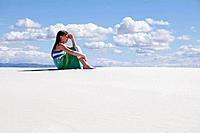 USA, New Mexico, Whitesands, Girl 10_11 sitting on desert and looking away
