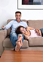 USA, New York State, New York City, young couple watching television on sofa