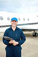 Mechanic holding clipboard with private jet in the background