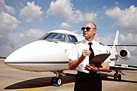 Pilot standing at runway holding a clipboard