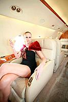 Woman siting in private jet holding a glass of champagne