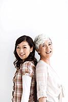 Portrait of mature woman and young woman standing back to back, smiling, white background