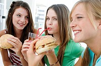 Close_up of three young women sitting in a restaurant and holding burgers